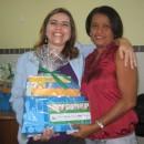 Autora Claudia Lins realizando entrega de livros para diretora de escola pública
